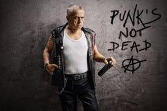 Punker masculino maduro que guarda um pulverizador da parede e que inclina-se contra uma parede cinzenta oxidada com o punk escri imagens de stock royalty free
