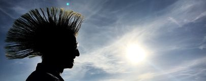 Punker silhouette. Punker hairstyle silhouette against blue sky royalty free stock photo