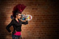 Punkmädchen auf Backsteinmauerhintergrund Stockbilder