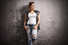 Punkowa dziewczyna opiera przeciw ośniedziałej szarości ścianie Fotografia Stock