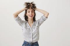 Punkrock inte absolut Ståenden av den roliga attraktiva kvinnan med sinne för humor som lyfter upp hår med händer som ser som, va Fotografering för Bildbyråer