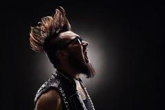 Punkrocker, der auf dunklem Hintergrund schreit Lizenzfreie Stockfotos