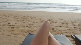 Punkt av sikten av den unga kvinnan som ligger på, sunbed vid havet och garva Kvinnligben på schäslongen som kopplar av och tycke lager videofilmer