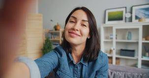 Punkt av sikten av flickan som tar selfie som ler att posera se kameran hemma arkivfilmer