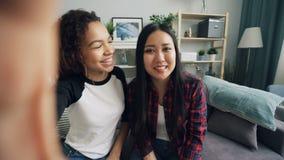 Punkt av sikten av gladlynta vänner som gör den online-videopd appellen som ser kameran, innehavapparaten, samtal och att göra en lager videofilmer