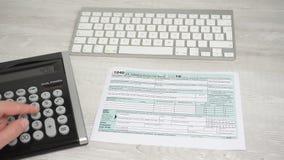 Punkt av siktsrörelse av formen för kvinnaläsningskatt 1040 och den beräknande skatteåterbäringen på skrivbordet bredvid datortan arkivfilmer