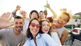 Punkt av siktsskottet av lyckliga vänner som tar selfe på taket på sommarpartiet som skrattar, poserar och tycker om det bra före arkivfilmer