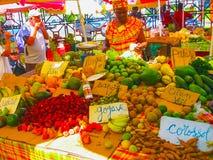 Punkt-en-Pitre Guadeloupe - Februari 09, 2013: kvinnan säljer nya frukter på den utomhus- marknaden i Guadeloupe Fotografering för Bildbyråer