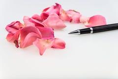 Punkt-Stift der schwarzen Kugel mit dem hellrosa rosafarbenen Blumenblatt auf weißem backgro Stockfotografie
