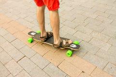 Punkt widzenia osoby noga na longboard na miasto ulicie P Fotografia Royalty Free