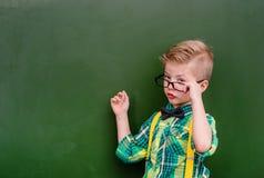Punkte des kleinen Jungen auf leerer grüner Tafel Stockfotografie