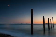 PunktRoberts pilings och silkeslent vatten på nattetid royaltyfria bilder