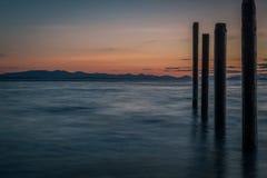 PunktRoberts pilings och silkeslent vatten på nattetid arkivfoton