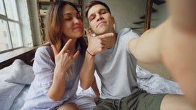 Punktu widzenia strzał bierze selfie wpólnie pozuje, całuje i ma zabawę kochająca para, podczas gdy siedzący na łóżku w domu zdjęcie wideo