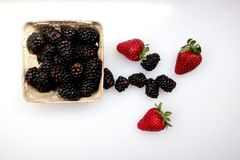 A punnet of blackberries and three fresh strawberries on a white background. A punnet of fresh blackberries, left of center, and three fresh strawberries, white stock photos