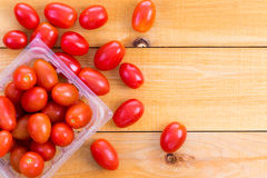 Punnet of fresh healthy baby tomatoes. Displayed on a wooden table with some spread around alongside , copy space to the side Stock Image