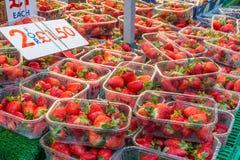Punnets av jordgubbar på skärm på ett stånd i regnet Royaltyfria Bilder