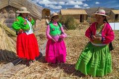 Puno, Перу - около июнь 2015: Женщины поя на острове и деревне Uros плавая на озере Titicaca около Puno, Перу Стоковые Фото