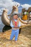 Puno, Перу - около июнь 2015: Малый мальчик в традиционных одеждах и шлюпке каное на острове и деревне Uros плавая на озере Titic стоковое изображение rf