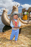 Puno, Peru - circa June 2015: Small boy in traditional clothes and canoe boat at Uros floating island and village on Lake Titicaca. Near Puno, Peru Royalty Free Stock Image