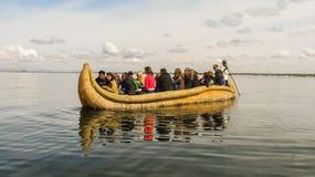 Puno Peru - Circa Maj 2014: Turister på ett traditionellt vassfartyg i sjön Titicaca nära Puno Royaltyfria Foton