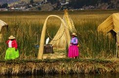 PUNO, PERU - 11 DE NOVEMBRO DE 2015: Mulheres em vestuários tradicionais em Uros Islands, lago Titicaca, Peru fotos de stock royalty free