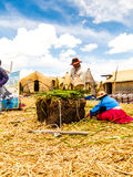 Puno, Peru - December 10, 2011: Two Uros working on Reed Stock Photography