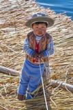 Puno, Peru - około Czerwiec 2015: Mała chłopiec w tradycyjnym odziewa przy Uros spławową wyspą i wioską na Jeziornym Titicaca bli Obrazy Royalty Free
