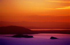 Puno Sunset Over Lake Titicaca. Colorful and beautiful Puno sunset over Lake Titicaca and Amantani Island, which includes the Pachamama Temple Royalty Free Stock Image