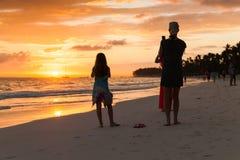 Tourists takes photos of sunrise. Punta Cana, Dominican Republic - January 5, 2017: Tourists takes photos of sunrise with smartphones, beach of Punta Cana Stock Photography