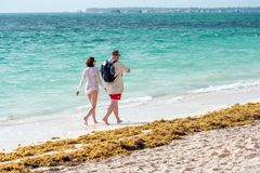 PUNTA CANA, DOMINICAN REPUBLIC - MAY 22, 2017: Couple walking along a sandy beach. Copy space for text. PUNTA CANA, DOMINICAN REPUBLIC - MAY 22, 2017: Couple Stock Photo