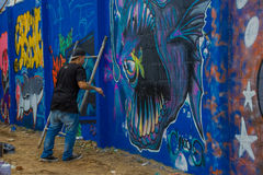 PUNTA DEL ESTE, УРУГВАЙ - 6-ОЕ МАЯ 2016: неопознанные люди с щеткой на руке крася некоторые детали на граффити стоковые изображения