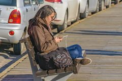Young Woman Listening Music at Boardwalk Royalty Free Stock Image