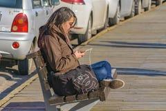 Young Woman Listening Music at Boardwalk. PUNTA DEL ESTE, URUGUAY, AUGUST - 2016 - Young woman listening music at boardwalk in Punta del Este city, Uruguay Royalty Free Stock Image