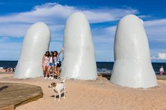 People at the sculpture La Mano in Punta Del Este, Uruguay. Punta Del Este, Uruguay - February 28th, 2018: Three young women taking photos and sefies at La Mano Royalty Free Stock Photos