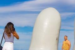 Woman taking a photo at La Mano, Punta Del Este. Punta Del Este, Uruguay - February 28th, 2018: Young woman taking a photo at La Mano, the sculpture made by Stock Images