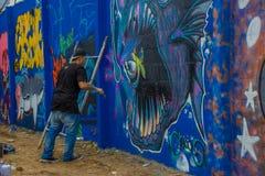 PUNTA DEL ESTE URUGUAY - MAJ 06, 2016: oidentifierade män med en borste på handen som målar några detaljer på grafitti arkivbilder