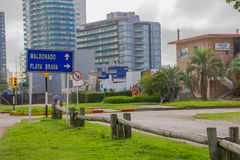 PUNTA DEL ESTE, URUGUAY - MAY 06, 2016: blue metal sign indicating the directions to the beach in the street with some buildings a Stock Photography