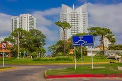 PUNTA DEL ESTE URUGWAJ, MAJ, - 06, 2016: ładna ulica z niektóre drzewami w chodniczkach i niektóre nowożytnych budynkach jako tło Zdjęcie Stock