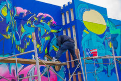 PUNTA DEL ESTE URUGWAJ, MAJ, - 06, 2016: młody człowiek stoi nad szafotem maluje graffiti Zdjęcie Royalty Free