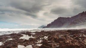 Punta del Hidalgo, Tenerife, Espania - October 27, 2018: Panorama of the rocky beach of Punta de Hidalgo and the waves breaking at. The rocks, taken on a rainy stock photos