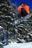 Punta del Snowboarder en usted durante un salto Imagen de archivo