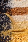 Punta su un insieme dei cereali sotto forma di bande orizzontali su un fondo nero Immagini Stock