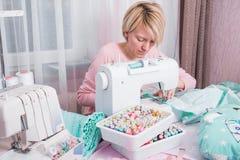 Puntada de la mujer en casa en la máquina de coser fotografía de archivo