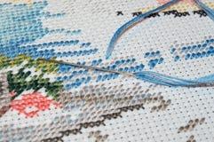 Puntada de media cruz hecha con el hilo azul Imagen de archivo