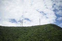 Puntal de la tecnología inalámbrica de las antenas de TV del palo de la telecomunicación en una cumbre de la montaña verde, del c foto de archivo