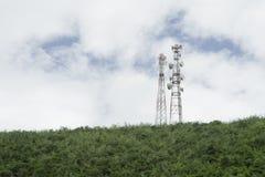 Puntal de la tecnología inalámbrica de las antenas de TV del palo de la telecomunicación en una cumbre de la montaña verde, del c foto de archivo libre de regalías