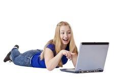 Puntas de la mujer joven sorprendidas al monitor del ordenador Imágenes de archivo libres de regalías