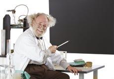 Puntas excéntricas sonrientes del científico a la pizarra fotografía de archivo libre de regalías