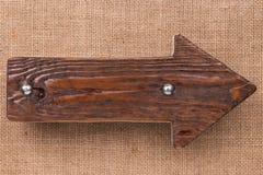 Puntatore fatto di legno scuro con i ribattini del metallo su tela da imballaggio Isolato su priorità bassa bianca Immagini Stock Libere da Diritti